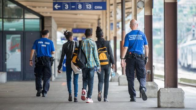 Grenzwächter begleiten MIgranten am Bahnhof Chiasso, 12.7.2016