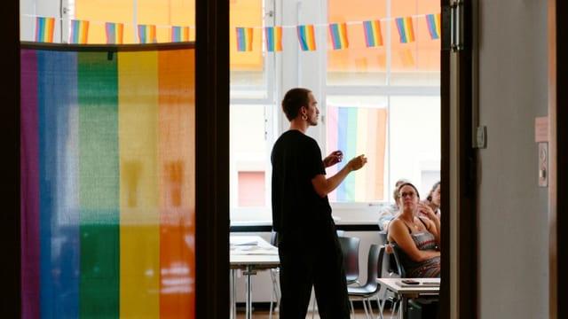 Ein Mann steht in einem Workshop-Raum voller Regenbogenflaggen.