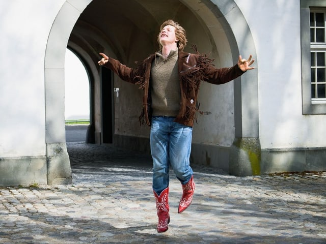 Ein junger Mann in Cowboy-Stiefeln springt in einem Innenhof umher.