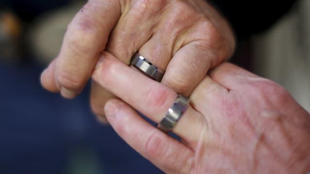 Zwei Männerhände bestückt mit den gleichen Eheringen
