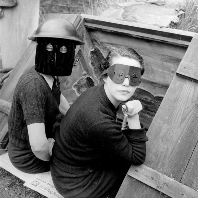 Schwarz-weiss-Aufnahme von zwei Frauen in Feurschutzmasken.