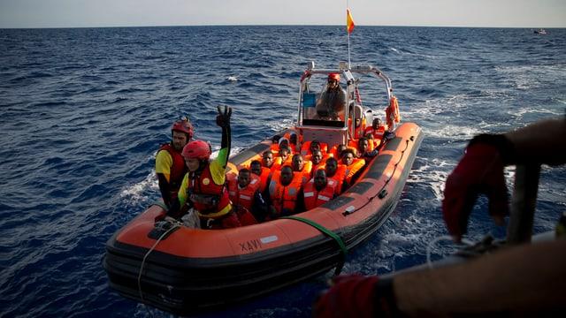 Fugitivs en ina bartga da salvament sin la mar mediterrana.