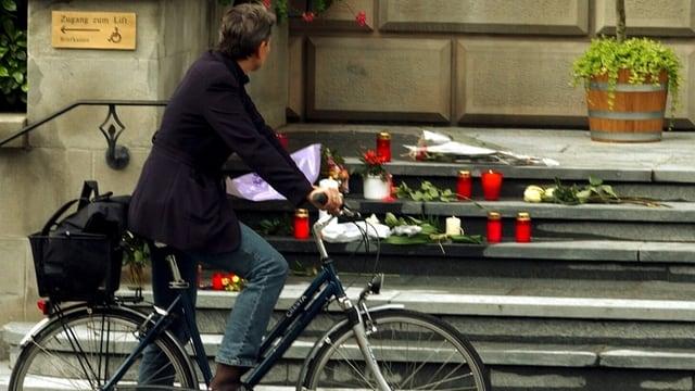 Ein Mann steht mit seinem Velo vor einer Treppe auf der Kerzen und Blumen liegen.