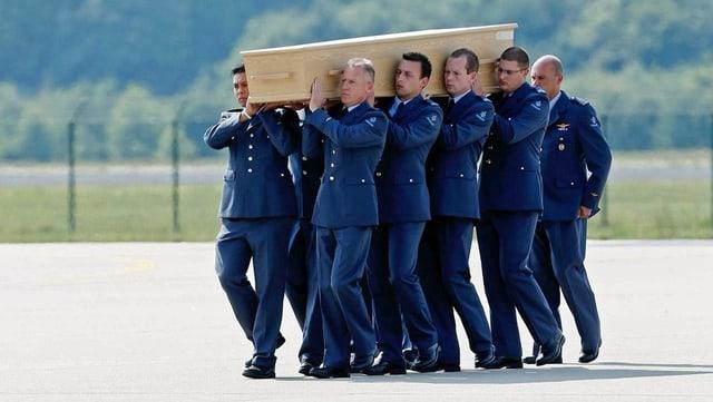 Soldaten tragen einen Sarg auf ihren Schultern.