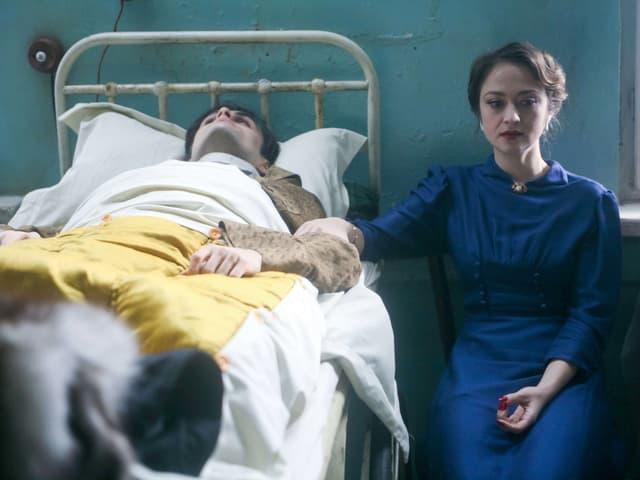 Ein Mann liegt im Krankenbett, neben ihm sitzt eine Frau in einem blauen Kleid. Sie hält ihn am Arm.