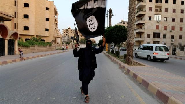 Ein IS-Kämpfer zieht mit erhobenem Gewehr und IS-Fahne in der Hand durch die Strassen Raqqas.
