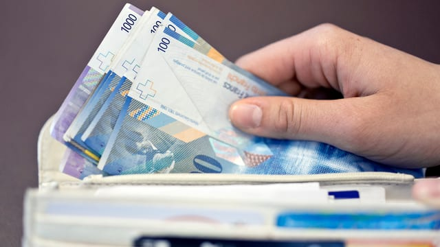 Hände nehmen Geldnoten aus Portmonaie; drei Hunderternoren und zwei tausendernoten sind zu sehen.
