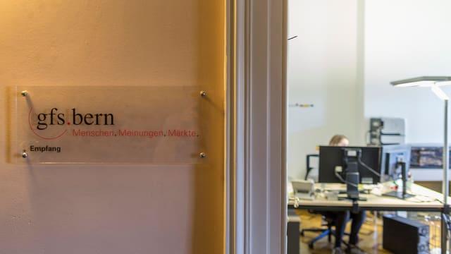 Ein Türschild mit dem Logo von gfs.bern vor einem Büro.