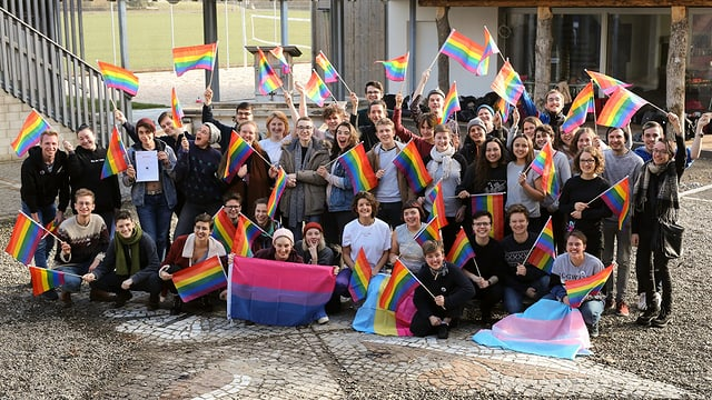 Eine Gruppe junger Menschen mit Regenbogenfahnen auf einem Kopfsteinpflasterplatz