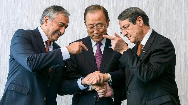 Drei Männer geben sich die Hände.