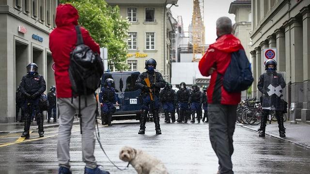 Polizists bloccheschan la via datiers d'ina demonstraziun da corona a Berna.