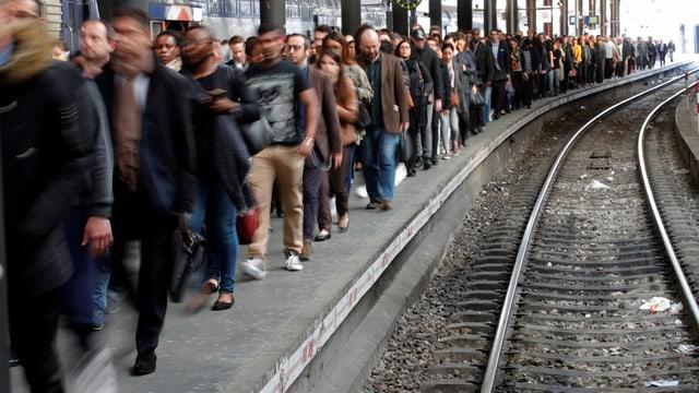 Vielen Menschen laufen auf einem Bahnperron ohne Zug