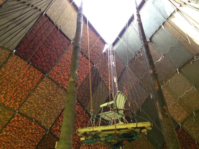 Zu sehen ist ein viele Meter hohes Zelt in der Innenansicht. An zwei Baumstämmen führt ein selbst gebauter Lift nach oben.