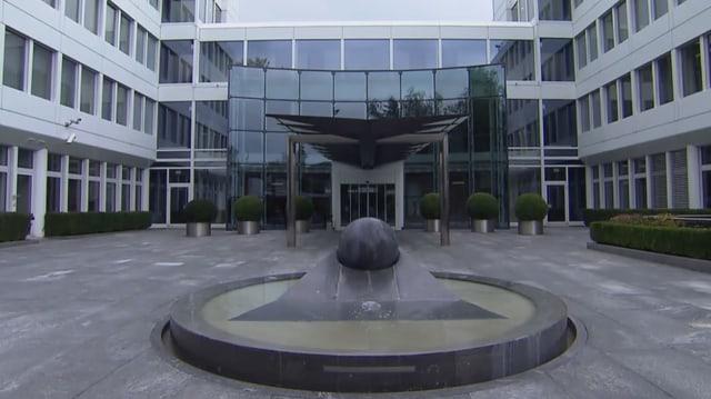 Gebäude mitSkulptur im Vordergrund.