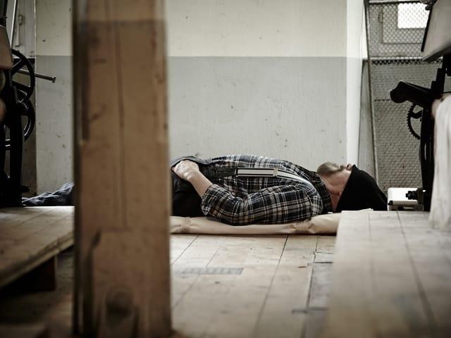 Adriano Geiger döst auf Holzboden in der Fabrik