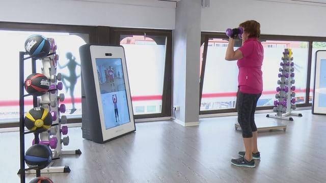 Saal ohne Geräte nur Bildschirm und Hanteln...Frau trainiert