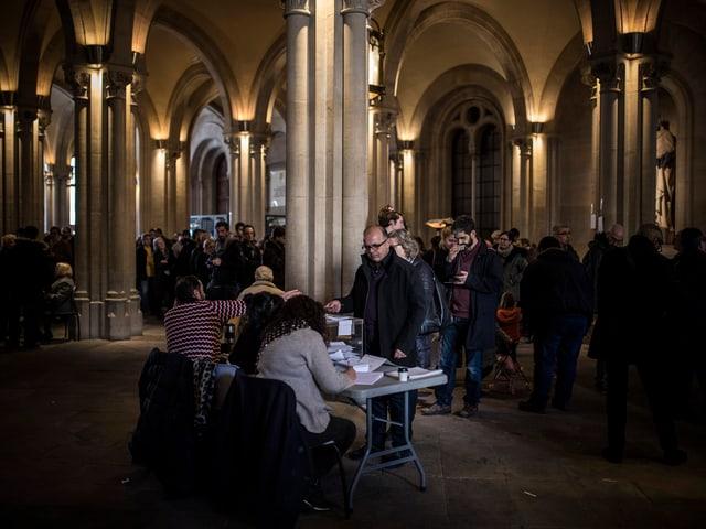 Tisch mit Urnen und Menschen.