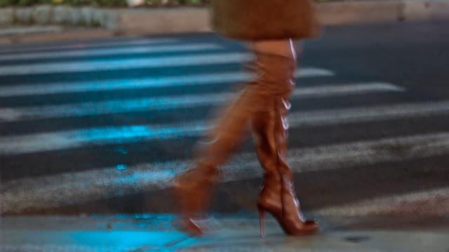 Eine Prostituierte wartet vor einem Fussgängerstreifen auf Kundschaft.