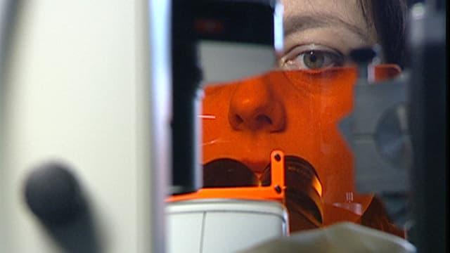 Nahaufnahme: Eine Forscherin blickt in ein Mikroskop.