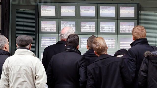 Menschen vor Bildschirmen mit Wirtschaftsnachrichten.
