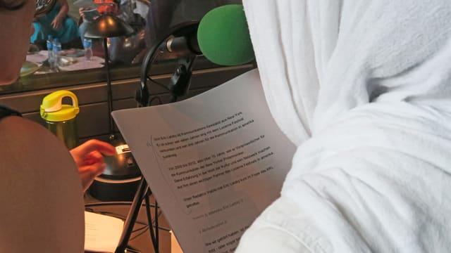 Eine junge Frau mit Kopftuch liest ihr Manuskript in einer Live-Radiosendung.