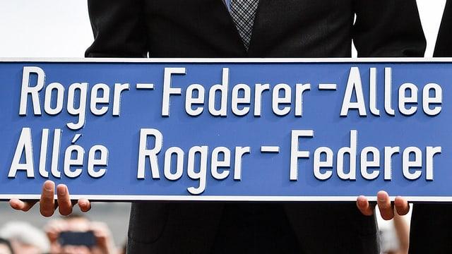 Federer mit Strassenschild in der Hand.