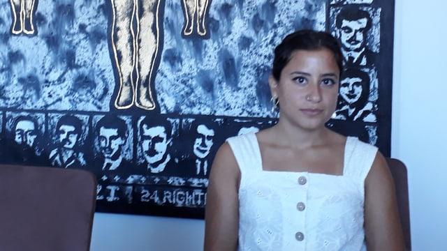 Aya Majzoub, eine junge Frau sitzt vor einem blauen Wandteppich.