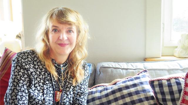 Monika Schmid sitzt auf dem Sofa in ihrem Wohnzimmer.