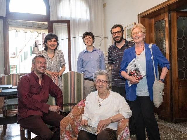 Sechs Personen posieren in einem Wohnzimmer