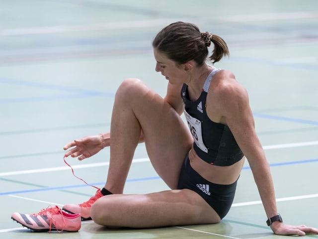 Lea Sprunger sitzt am Boden und öffnet ihre Schuhe.