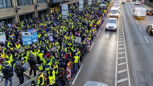 Menschen in Gelben Westen blockieren eine Strasse.