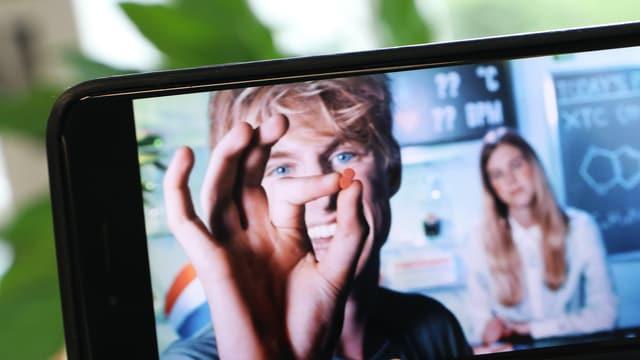 Ein Smartphone mit einem Foto: darauf hält ein Mann eine Tablette.