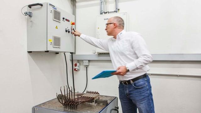 Mann dreht an Knopf einer Maschine, darunter Kabel auf einem Tisch