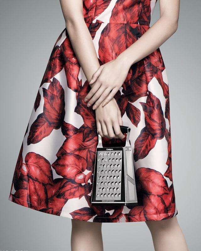 Frau trägt weisses Kleid mit roten Blättern und hält Gemüseraffel in der Hand.