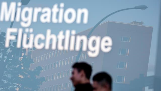 Purtret cun funs blau grisch e scrit si davant «Migration Flüchtlinge».