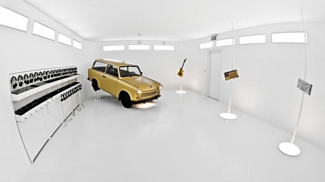 Ein weisser Museumsraum: darin scheint ein gelbes Auto zu schwebe. Daneben hängen viele Kopfhörer.