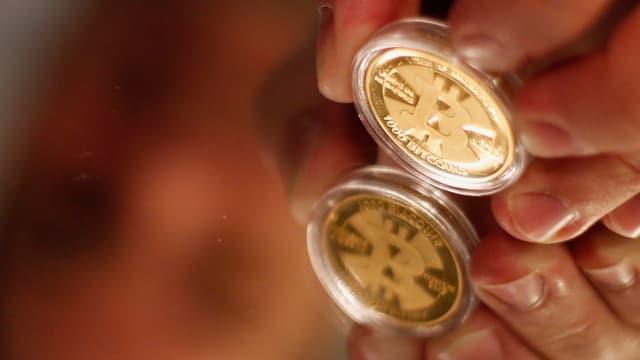 Finger halten eine Bitcoin-Münze, die sich in einem Tisch spiegelt.