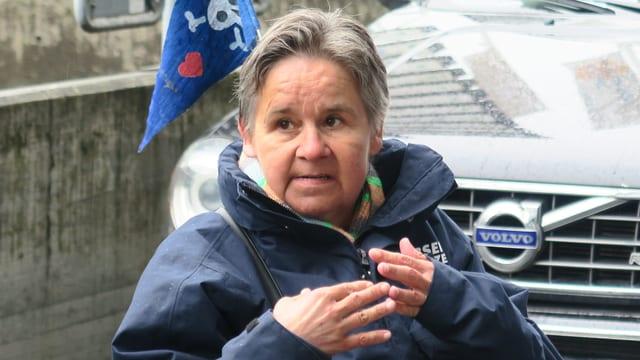 Eine ältere Frau mit grauen, kurzen Haaren sitzend.