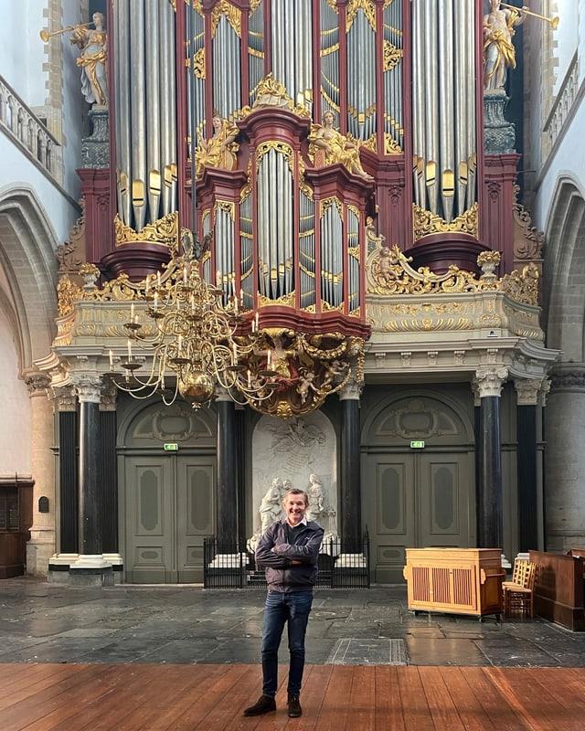 ein Mann steht vor einer imposanten Orgel