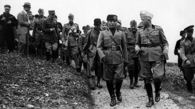 Schwarzeweissfoto: Mussolini geht neben General Badoglio einer Soldatentruppe voran.