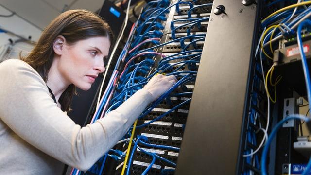 Eine Frau steht vor einen Schrank mit vielen Kabeln.