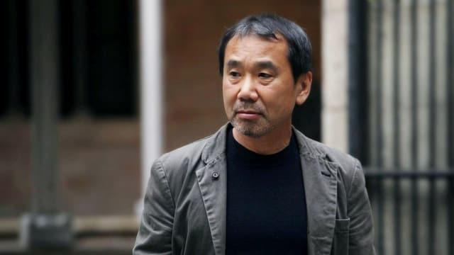 Murakami steht draussen vor einem Gebäude.