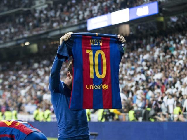 Lionel Messi zeigt den Real-Fans demonstrativ die Rückseite seines Trikots.