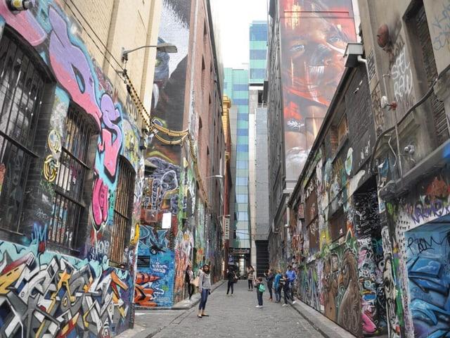 Eine Gasse zwischen Häusern, vollgesprayt mit Graffitis, in der Gasse sind Menschen unterwegs.