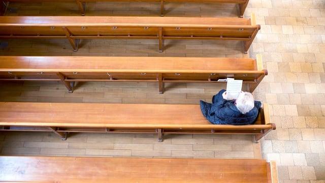 Eine alte Person sitzt in der Kirche und hält ein Gesangsblatt in der Hand.
