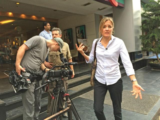 Barbara Lüthi und ihr Kamerateam vor einem grossen Gebäude in Kolkata.
