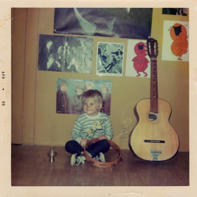 Kurt Cobain als kleiner Junge, neben einer Gitarre sitzend.