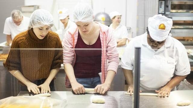 Zwei junge Frauen versuchen sich in der Bäcker-Arbeit an der Berufsmesse Zürich