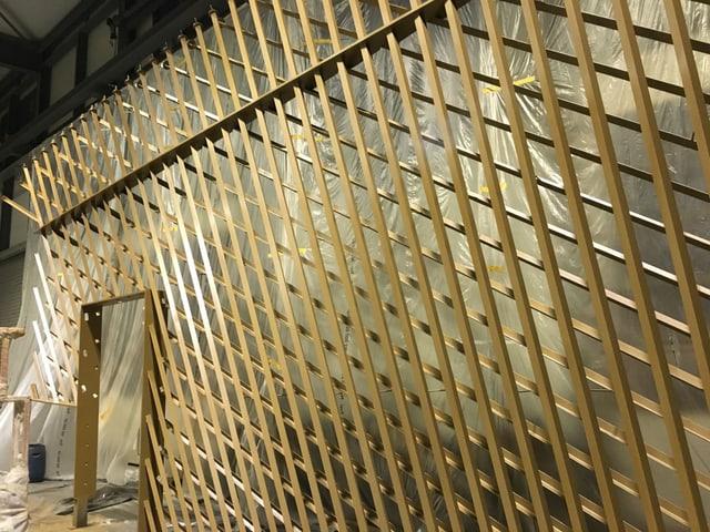 Eine goldene Wand aus Stahlstäben.