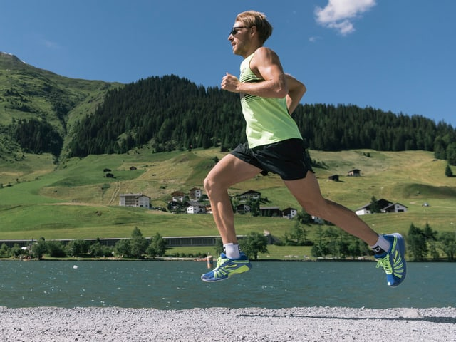 Ein Mann rennt auf einer Strasse, dahinter ein See.
